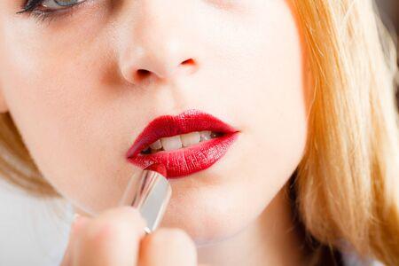 rubia ojos azules: Retrato de una mujer hermosa aplicar el lápiz labial