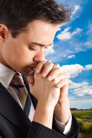 Young religious man praying outdoor  photo