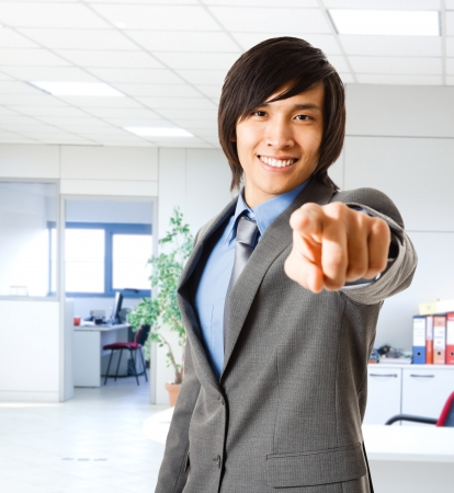 Portrait of a smiling asian businessman pointing his finger at you photo