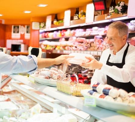 oficinista: Tendero atendiendo a un cliente en una tienda de comestibles