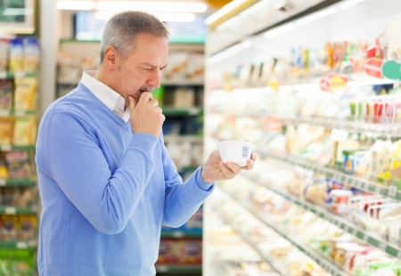 better price: Man comparing products at the supermarket