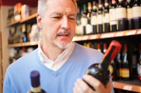 vintage bottle: Man in a supermarket comparing two wines Stock Photo