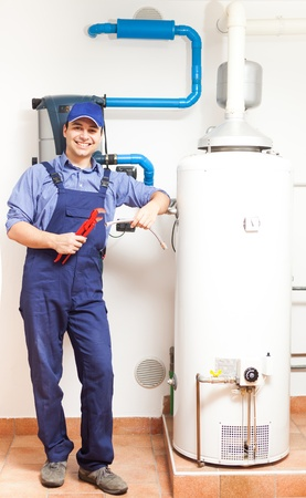 heater: Smiling technician repairing an hot-water heater Stock Photo