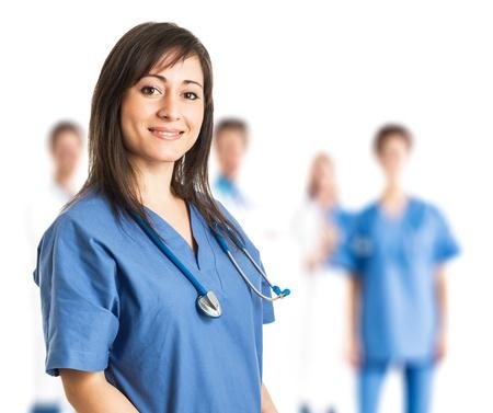 pielęgniarki: Portret uÅ›miechniÄ™ta mÅ'oda pielÄ™gniarka z przodu jej zespoÅ'u
