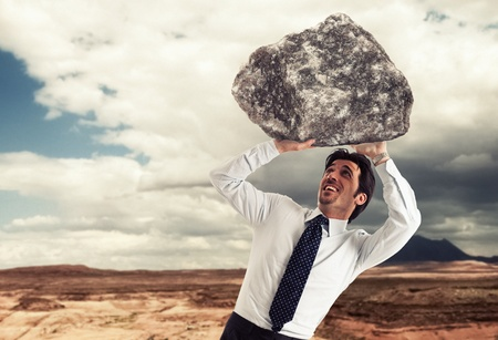 burdened: Stressed businessman trying to lift a rock