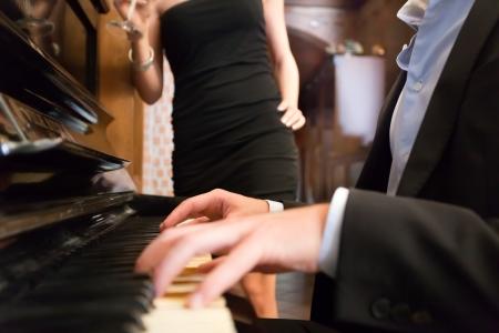 serenata: Hombre tocando el piano para su novia Foto de archivo