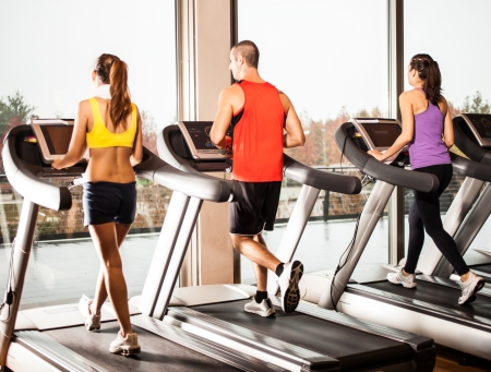 Gropu of people running on treadmills photo