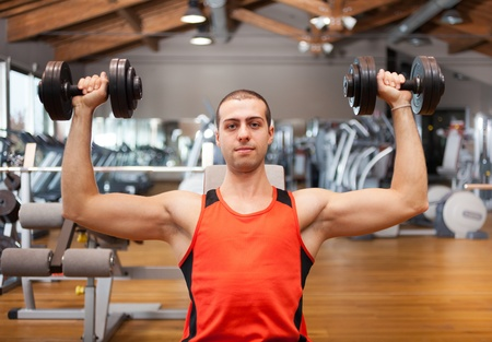 Man lifting a weight in a fitness club photo