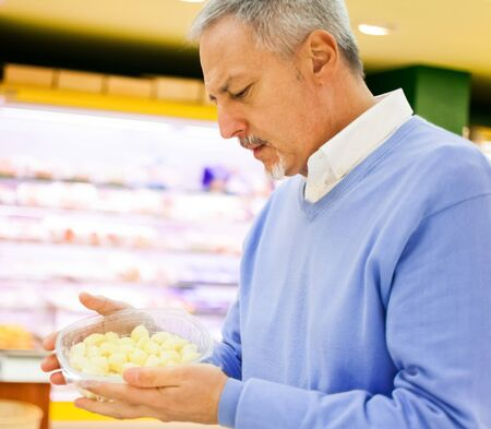 Man looking at a product in a supermarket Stock Photo - 17184532