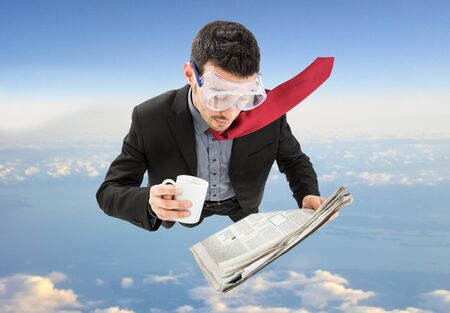 Portrait of a funny businessman skydiving while reading a newspaper photo