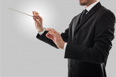 Orchestra conductor directing with his baton photo