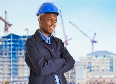 Portrait of a smiling black worker in front of a construction site photo
