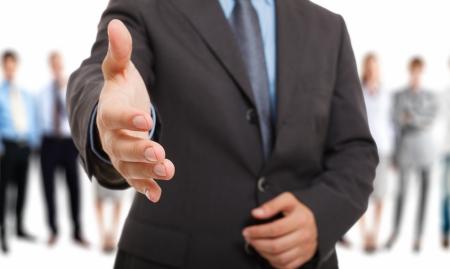 bienvenidos: Hombre de negocios que ofrece un apret�n de manos Foto de archivo