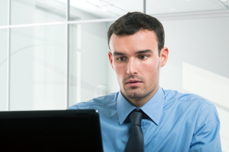 serious guy: Portrait of a businessman using his personal computer