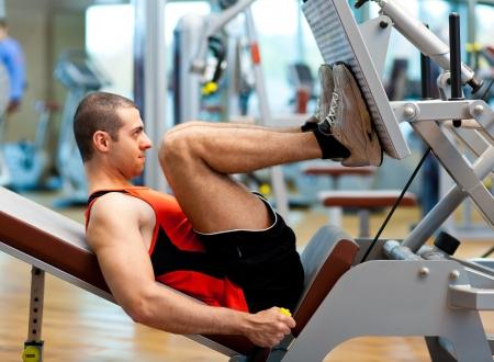 piernas hombre: Hombre haciendo fitness en un gimnasio Foto de archivo