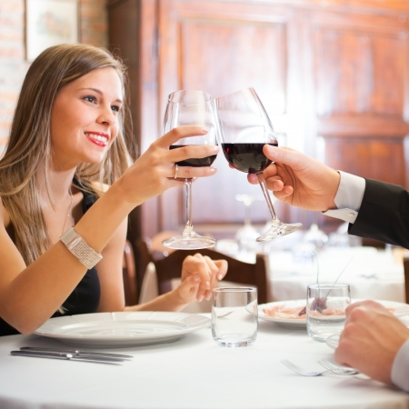 Couple toasting wineglasses in a luxury restaurant photo
