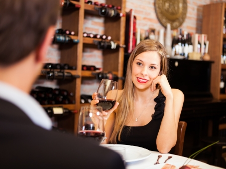 romantic evening with wine: Couple toasting wineglasses in a luxury restaurant