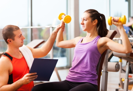 sports hall: Personal trainer showing an exercise to a woman