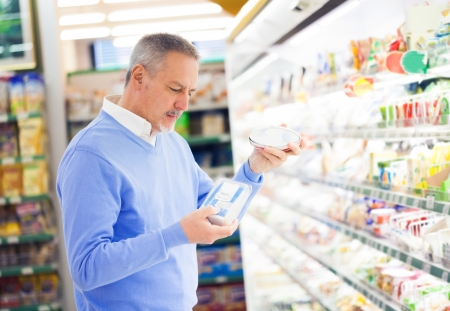 Man comparing products at the supermarket Stock Photo - 17420002