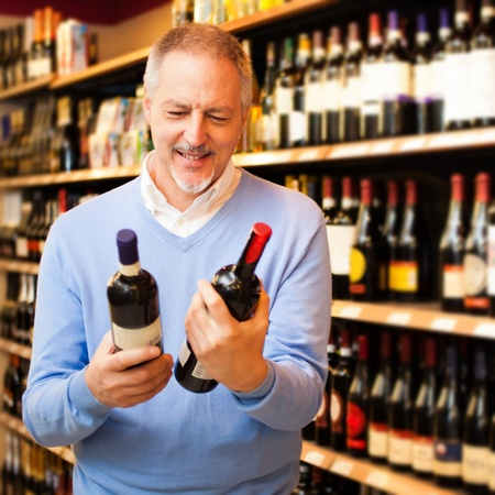wine store: Man in a supermarket choosing the right wine