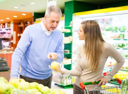 Woman holding an apple in a supermarket Stock Photo - 17420189