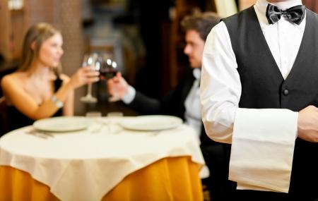 číšník: Pár na večeři v restauraci Reklamní fotografie