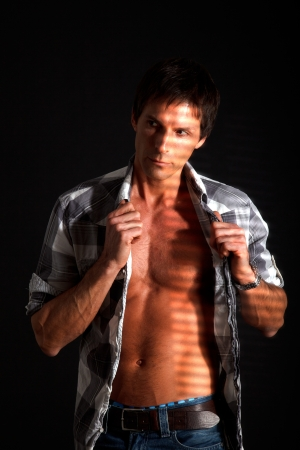 Adult attractive man posing against a dark background  photo