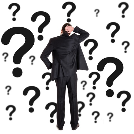 Thoughtful man surrounded by question marks photo