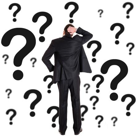 punto interrogativo: Uomo riflessivo, circondato da punti interrogativi