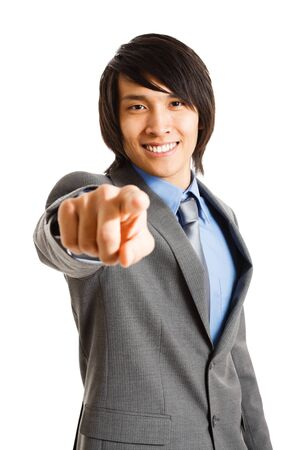 Portrait of a smiling asian businessman pointing his finger at you  Isolated on white photo