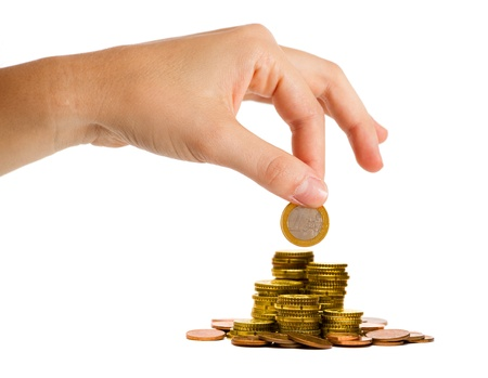growing money: Money save concept: hand putting a coin on the top of a money pile