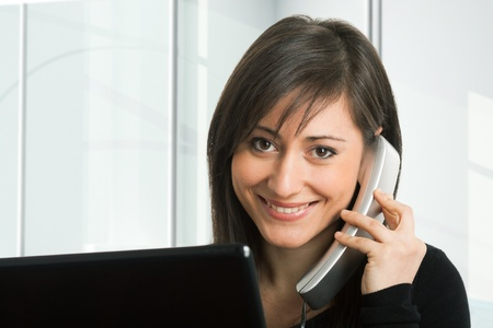 Portrait of a woman in front of her monitor while talking on the phone Stock Photo - 17696417