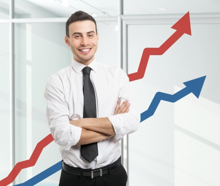 investor: Portrait of an happy businessman standing in front of rising arrows Stock Photo