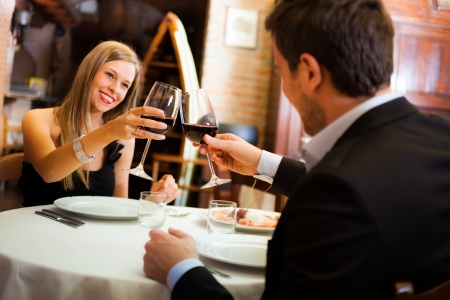 romantic evening with wine: Couple toasting wineglasses in a restaurant