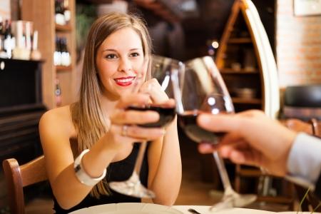diner romantique: Verres à vin grillage couple dans un restaurant Banque d'images