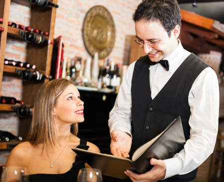 suggesting: Waiter suggesting food to a woman in a restaurant