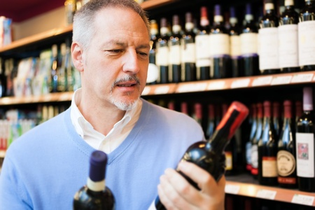 Man in a comparing two wines bottles photo