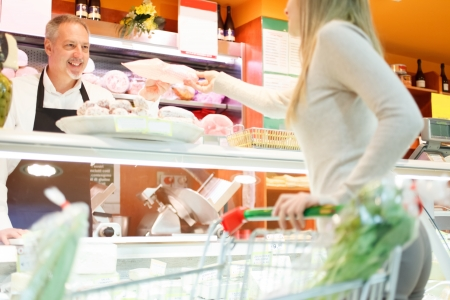 sales assistant: Shopkeeper serving a customer in a grocery store