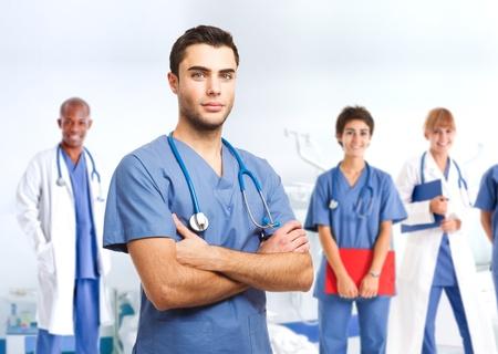 estudiantes medicina: Retrato de un apuesto médico frente a su equipo médico