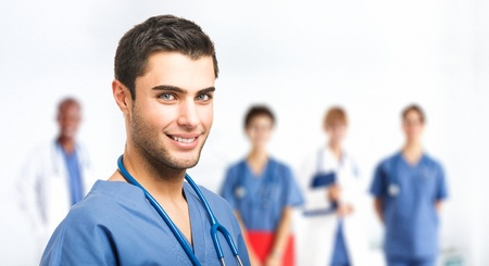 traineeship: Portrait of an handsome doctor in front of his medical team Stock Photo