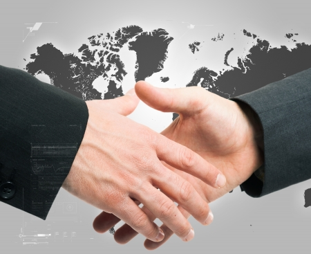 international business agreement: Businessmen shaking hands against an hi-tech background Stock Photo