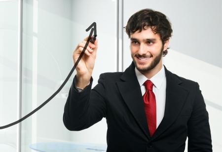 productividad: Hombre dibujando una flecha ascendente en el vidrio