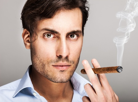 serious guy: Portrait of a confident man smiking a cigar