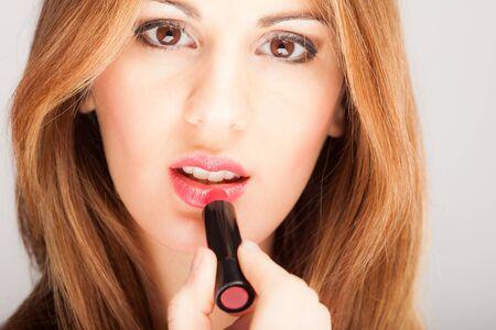 pink lips: Beautiful woman applying lipstick