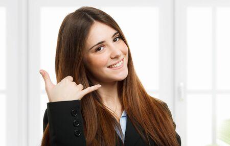 amigas conversando: Amable mujer imitando una llamada de teléfono con la mano
