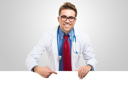 Smiling doctor showing a white board Stock Photo - 18468242