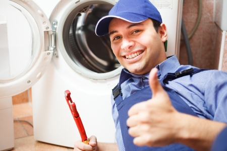 repairmen: Portrait of a technician repairing a washing machine