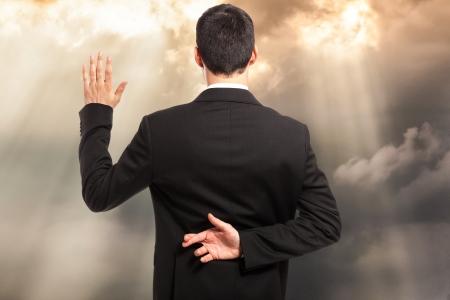 hipocresía: Jurar con los dedos cruzados detr�s de la espalda Foto de archivo