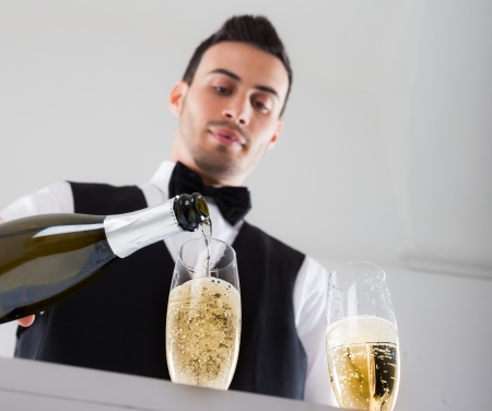 serve: Portrait of a waiter pouring champagne into a flute