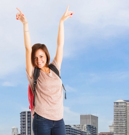 Portrait of an happy teenager raising her arms photo